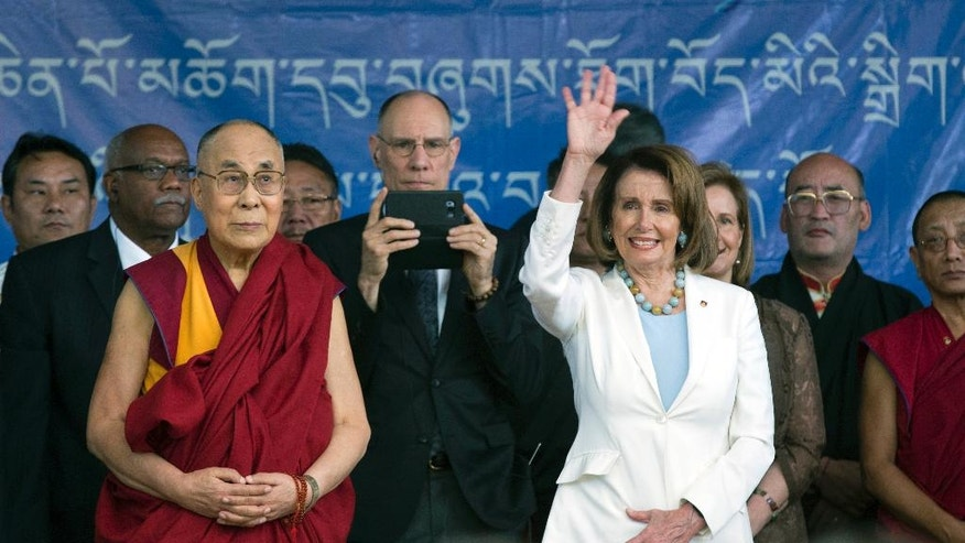"Democratic leader in the U.S. House of Representatives Nancy Pelosi waves to a crowd as she stands next to the Tibetan spiritual leader Dalai Lama at the Tsuglagkhang temple in Dharmsala, India, Wednesday, May 10, 2017. A group from US Congress is taking aim at one of China's sore spots, Tibet, during a meeting in India with the Tibetan Buddhist spiritual leader. Pelosi said Wednesday that China was using ""brutal tactics"" and economic leverage to crush Tibetan calls for autonomy. (AP Photo/Ashwini Bhatia)"