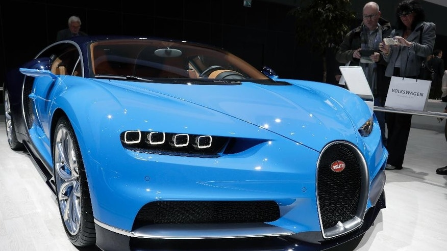 People stand at a Bugatti Chiron car during the annual shareholders meeting of the Volkswagen AG in Hannover, Germany, Wednesday, May 10, 2017. (AP Photo/Michael Sohn)