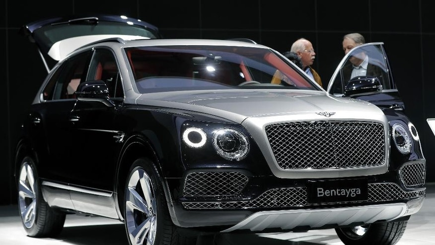 People stand at a Bentley Bentayga SUV car during the annual shareholders meeting of the Volkswagen AG in Hannover, Germany, Wednesday, May 10, 2017. (AP Photo/Michael Sohn)