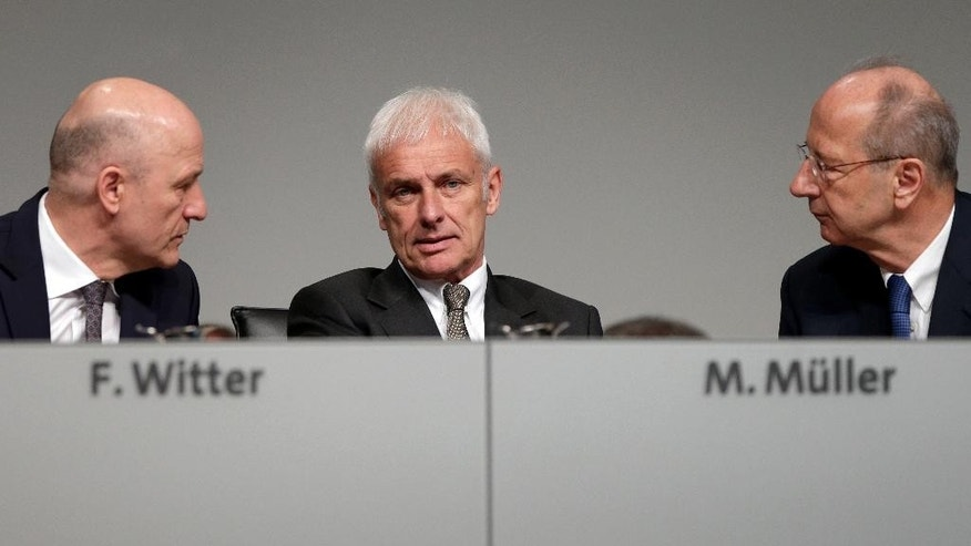 From left, Frank Witter, CFO of the Volkswagen AG, Matthias Mueller, CEO of the Volkswagen AG, and Hans Dieter Poetsch, chairman of the board of directors of the Volkswagen AG, talk prior to the annual shareholders meeting in Hannover, Germany, Wednesday, May 10, 2017. (AP Photo/Michael Sohn)