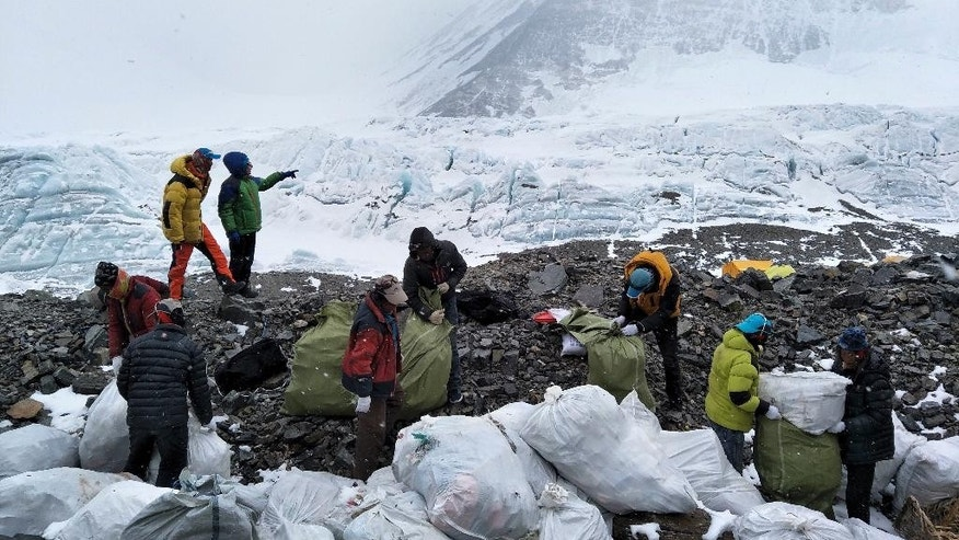 In this Monday, May 8, 2017 photo released by Xinhua News Agency, people collect garbage at the north slope of the Mount Qomolangma in southwest China's Tibet Autonomous Region. Workers and volunteers collected four tons of garbage from the Chinese north side of Mount Everest in the first five days of a cleanup operation, state media reported Thursday, May 11, 2017. (Awang Zhaxi/Xinhua via AP)