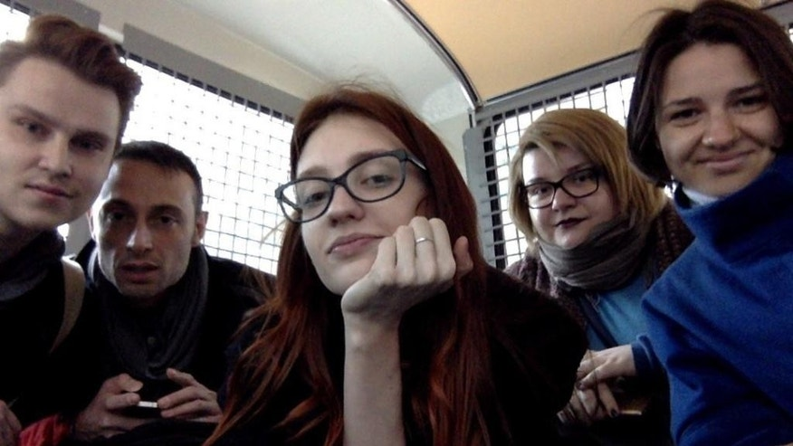In this photo provided by Nikita Safronov, Russian activist and journalist Nikita Safronov, left, and his friends make a selfie inside a police van, after being detained in Moscow, Russia, Thursday, May 11, 2017. Several activists who were planning to submit signatures they have collected to protest arbitrary detentions and torture of gay men in Chechnya have been detained in Moscow. (Nikita Safronov photo via AP)