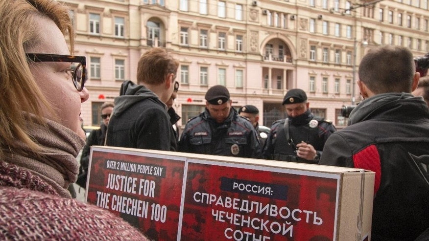 Russian police officers detain activists carrying boxes with signatures collected to protest the treatment of gay people in Chechnya, to the Prosecutor General's Office in Moscow, Russia, Thursday, May 11, 2017. Several activists were detained in Moscow on Thursday as they prepared to submit signatures they have collected to protest arbitrary detentions and torture of gay men in Chechnya. (Arden Arkman/Hanout Photo via AP)