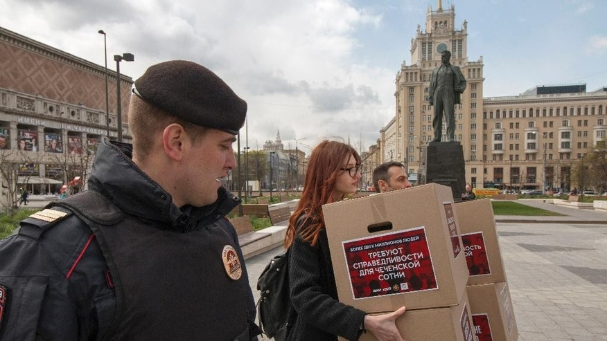 A Russian police officer looks at activists holding boxes with signatures collected to protest the treatment of gay people in Chechnya, in Moscow, Russia, Thursday, May 11, 2017. Several activists were detained in Moscow on Thursday as they prepared to submit signatures they have collected to protest arbitrary detentions and torture of gay men in Chechnya. In the back is a monument to Russian poet Vladimir Mayakovsky. (Arden Arkman/Hanout Photo via AP)