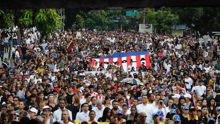 People gather for a homage to Miguel Castillo at the spot where he died yesterday in Caracas, Venezuela, Thursday, May 11, 2017. Castillo, 27, was killed during an anti-government protest when security forces dispersed thousands of people marching to the Supreme Court to reject a government initiative to rewrite the constitution. (AP Photo/Ariana Cubillos)