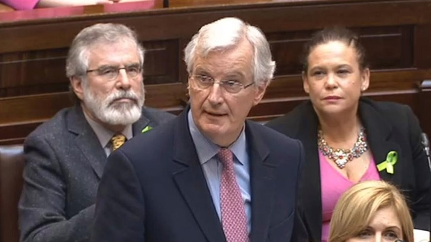 In this photo taken from video EU chief negotiator on Brexit Michel Barnier addresses Ireland's parliament at the Houses of the Oireachtas, in Dublin, Ireland, Thursday, May 11, 2017. ?The European Union's chief Brexit negotiator has reassured Ireland that the bloc will fight to ensure there is no return to a hard border with Northern Ireland when the U.K. leaves the bloc. Sein Fein's Gerry Adams sits in the background (Houses of the Oireachtas/PA via AP)