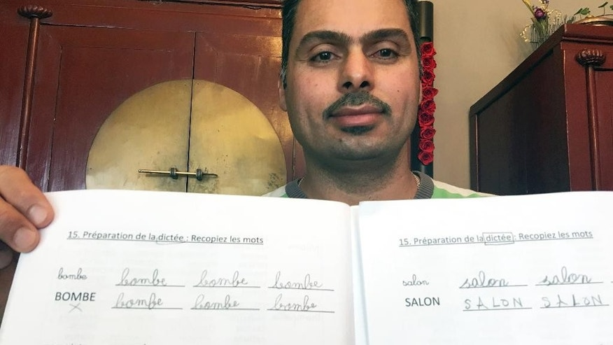 Iraqi refugee Raad Al Azzawi shows a lesson book at the house of his Belgian French tutor in Anderlecht, Belgium on Thursday, May 11, 2017. Read Al Azzawi and his tutor are both dismayed to have been given a French lesson book with references to bomb throwers and jails, suggesting that migrants might be extremists. (AP Photo/Sylvain Plazy)