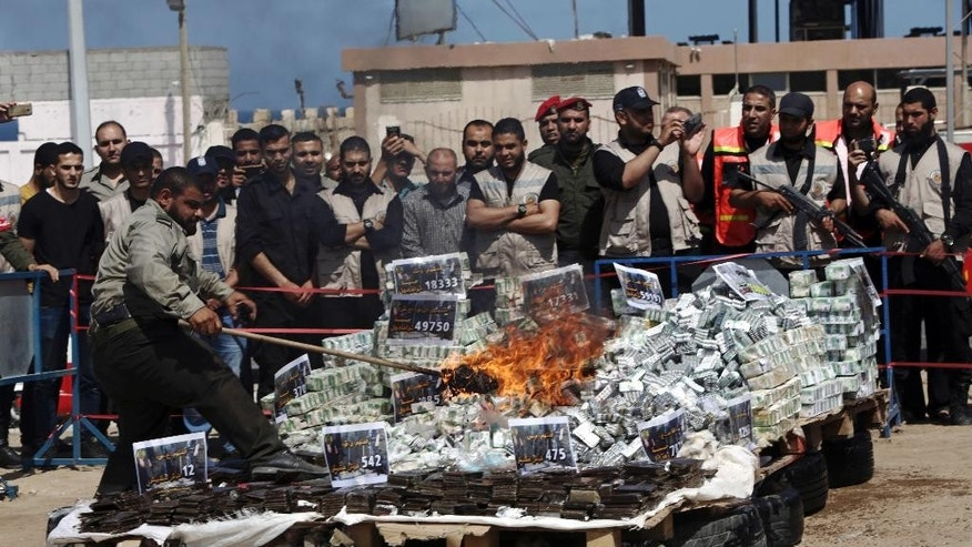Spectators watch as an officer of  the Hamas security forces burns some 1,130 bars of hashish and 467,000 pills that had been seized since the beginning of the year, in Gaza City, Thursday, May 11, 2017. Gaza's militant Islamic Hamas rulers also sentenced two dealers to death as part of their campaign against drugs. Thursday marked the second time Hamas has delivered death sentences for drug dealing since the group overtook Gaza by force in 2007. (AP Photo/Adel Hana)