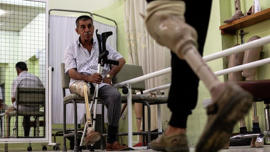 In this Wednesday, May 10, 2017 photo, a man watches another another patient practice walking on his prosthetic leg in the International Committee of the Red Cross prosthetics clinic in Irbil, Iraq.  The fight to retake Mosul has left more than 12,000 civilians injured and for many that has meant the loss of a limb.  (AP Photo/Bram Janssen)