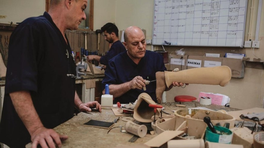 In this Wednesday, May 10, 2017 photo, technicians in the International Committee of the Red Cross clinic in Irbil work on a prosthetic leg. The clinic receives more than 450 new patients per month. (AP Photo/Bram Janssen)