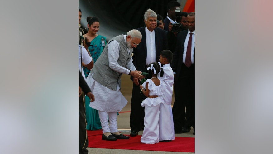 Indian Prime Minister Narendra Modi receives betel leaves from two Sri Lankan children upon his arrival as Sri Lankan Prime Minister Ranil Wickremesinghe, center watches in Colombo, Sri Lanka, Thursday, May 11, 2017. (AP Photo/Eranga Jayawardena)