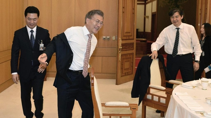 South Korean President Moon Jae-in, second from left, takes off his jacket at the presidential Blue House in Seoul, South Korea, Thursday, May 11, 2017. South Korean internet users have shared photos of Moon waving off a presidential employee and taking off his own jacket at a luncheon, projecting an image that he's a down-to-earth president. (Baek Seung-ryul/Yonhap via AP)