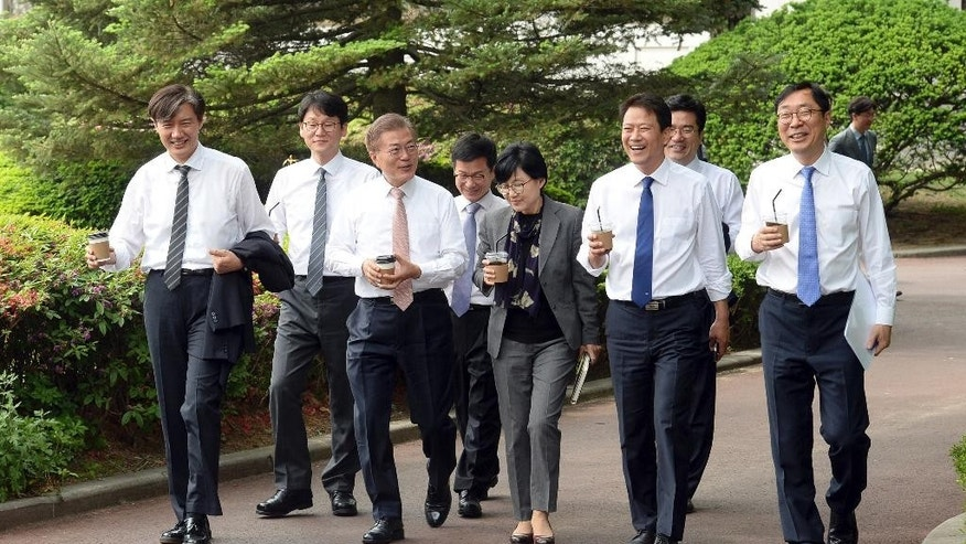 South Korean President Moon Jae-in, third from left, walks with senior presidential secretaries at the presidential Blue House in Seoul, South Korea, Thursday, May 11, 2017. South Korean internet users have shared photos of Moon waving off a presidential employee and taking off his own jacket at a luncheon, projecting an image that he's a down-to-earth president. (Baek Seung-ryul/Yonhap via AP)