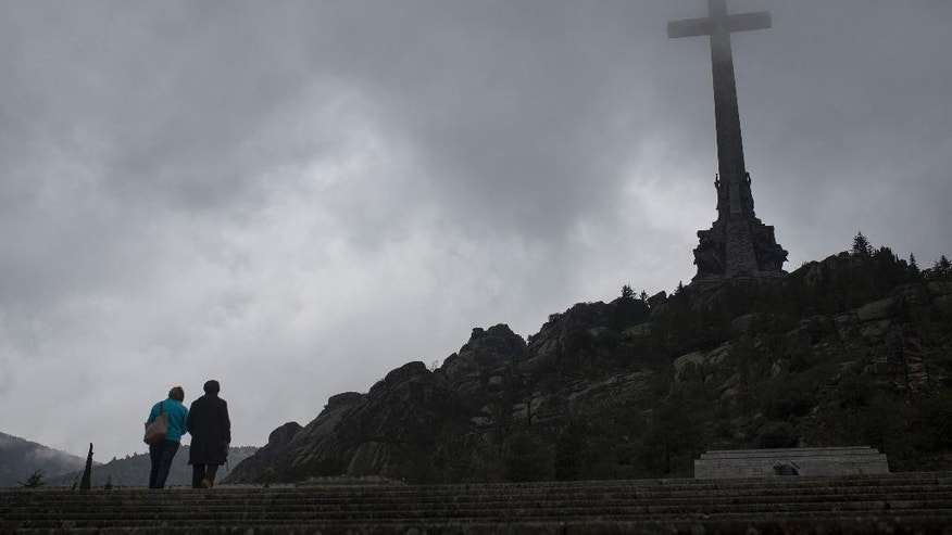 FILE - In this May 10, 2016 file photo, tourists walk outside the Valle de los Caidos (Valley of the Fallen) monument that houses the tomb of Spanish former dictator General Francisco Franco in it's mausoleum,near Madrid, Spain. Spanish lawmakers on Thursday, May 11, 2017, have voted in favor of moving the remains of dictator Gen. Francisco Franco from the Valley of the Fallen mausoleum, a measure that has long been rejected by the conservative governing Popular Party and has reopened debate relating to one of Spain's most painful episodes, the 1936-39 Civil War and its aftermath. (AP Photo/Francisco Seco, File)