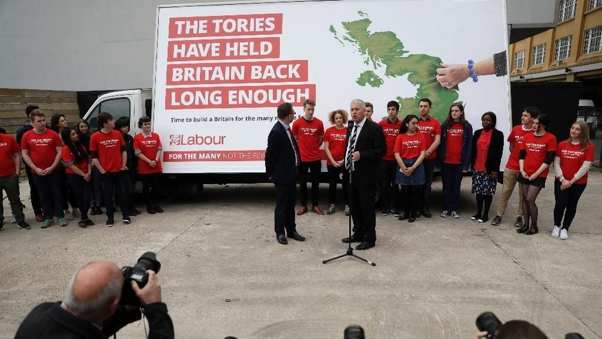 British opposition Labour Party member of Parliament Ian Lavery, at microphone, speaks flanked by Labour MP Andrew Gwynne and supporters during the Labour party's first campaign poster launch for the upcoming general election, which their leader Jeremy Corbyn did not attend, in London, Thursday, May 11, 2017. (AP Photo/Matt Dunham)
