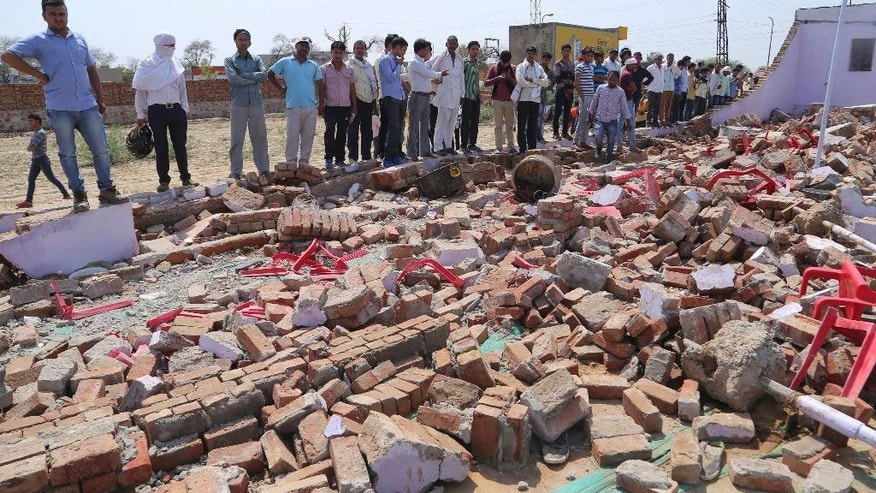 People look at the debris after a building wall collapsed onto guests at a wedding in western India.