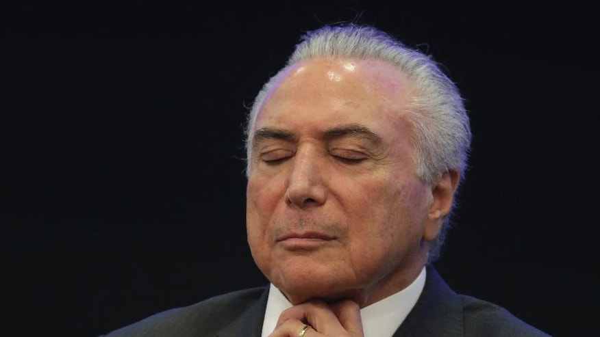 Brazil's President Michel Temer closes his eyes during a event at the Brazilian Institute of Research in Brasilia, Brazil, Monday, May 8, 2017. Temer promised to unify a fractured society, pull the economy from recession and create jobs. Now, Temer is very unpopular, unemployment is up and his reform agenda is very much in doubt. (AP Photo/Eraldo Peres)