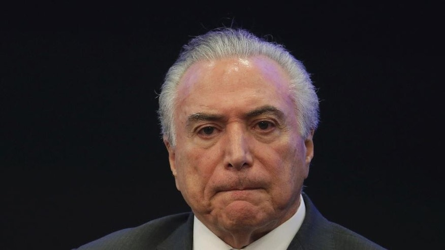 Brazil's President Michel Temer listens in during a event at the Brazilian Institute of Research in Brasilia, Brazil, Monday, May 8, 2017. A year after taking power amid a bitter impeachment battle, the promises by Brazilian President Michel Temer are on hold or lost.  (AP Photo/Eraldo Peres)