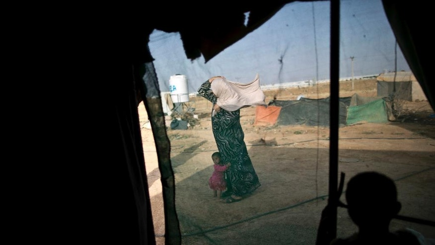 FILE -- In this June 3, 2016 file photo, a Syrian refugee holds on to her headscarf against the wind while she and her daughter stand outside their tent at an informal tented settlement near the Syrian border, on the outskirts of Mafraq, Jordan. Aid officials say Jordan has sent hundreds of Syrian refugees  back to Syria since the beginning of the year.'back to southern Syria in the first four months of 2017, an apparent spike in what a rights group says is a violation of international law. Deportees interviewed by The Associated Press say women and children are among those sent back, some expelled without apparent reason or due process. A Jordanian official confirms deportations are taking place, but says refugees are only deported for security reasons. (AP Photo/Muhammed Muheisen, File)