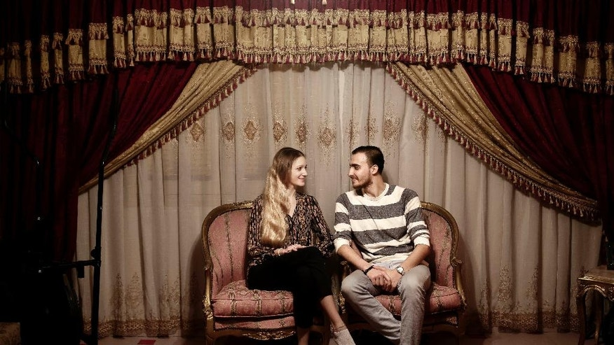 In this April 15, 2017 photo, ballet dancer Fady el-Nabarawy, right, and his Serbian fiancee, ballerina Kristina Lazovic, pose for a photograph at his home on the top floor of a six-story walk-up in the Omraniyah district of Cairo, Egypt. The national ballet company is rebuilding after years of political turmoil and economic pain. Ballet may be an elite Western art, it may be far removed from Egyptian society, which has grown more religiously conservative and xenophobic. But it's still a powerful passion for the Egyptians who dance it and watch it. (AP Photo/Nariman El-Mofty)