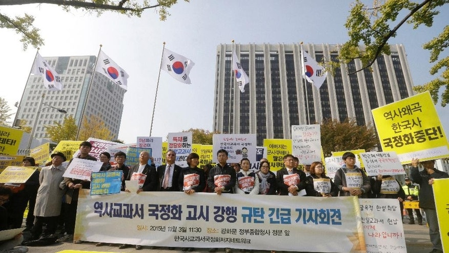 "FILE - In this Nov. 3, 2016, file photo, protesters stage a rally against the revision of the publication system for Korean history textbooks in front the government complex in Seoul, South Korea. New President Moon Jae-in has scrapped a controversial plan to introduce state-issued history textbooks at schools, erasing a key policy of his ousted conservative predecessor Park Geun-hye, Moon's office said Friday, May 12, 2017. The banner reads: ""We denounce government pushing ahead the announcement of publishing state-authored Korean history textbooks."" (AP Photo/Ahn Young-joon, File)"
