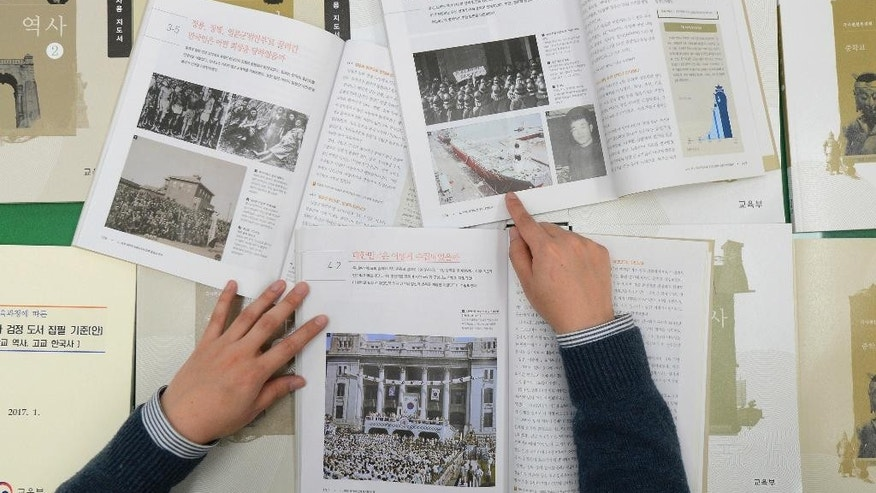 In this Jan. 31, 2017 photo, a government officer shows the final version of state-authored history textbooks unveiled at the government complex in Sejong, South Korea. New President Moon Jae-in has scrapped a controversial plan to introduce state-issued history textbooks at schools, erasing a key policy of his ousted conservative predecessor Park Geun-hye, Moon's office said Friday, May 12, 2017.(Kang Jong-min/Newsis via AP)