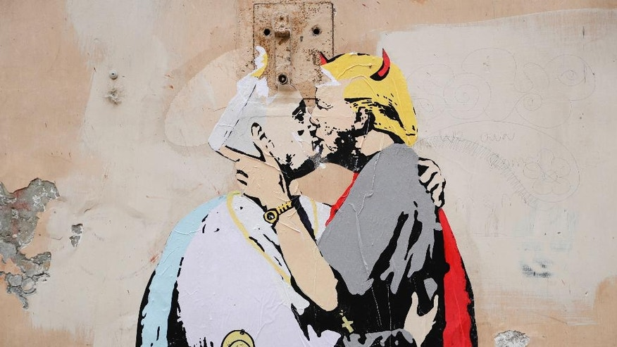 "A poster showing Pope Francis kissing a devilish, gun-toting Donald Trump is seen on a wall in Rome, Thursday, May 11, 2017. The poster has appeared in Rome less than two weeks before the first meeting between the pontiff and President Trump and is captioned with writing reading in English and Italian ""The Good forgives the Evil"" in tiny letters along Francis' belt. (AP Photo/Alessandra Tarantino)"