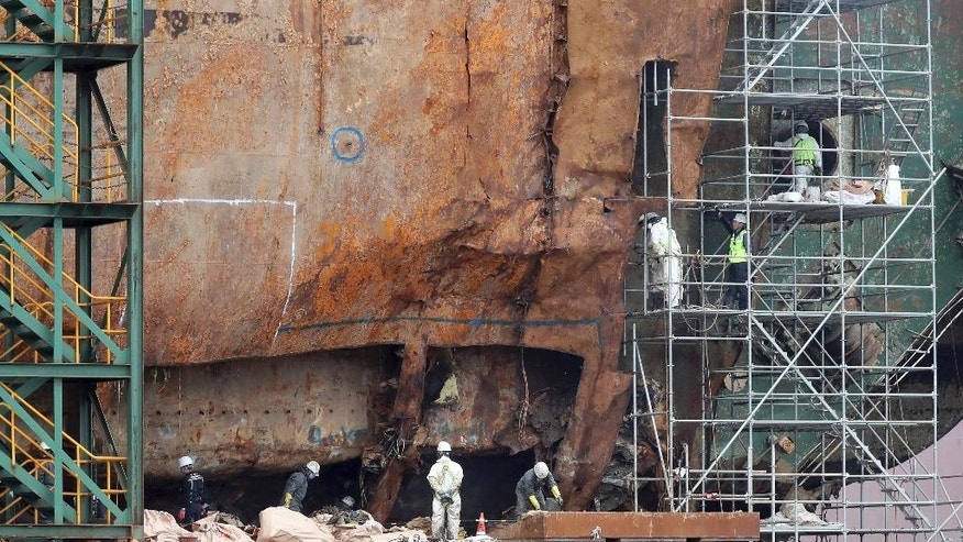 Workers search for bone fragments from the wreckage of the salvaged ferry Sewol at a port in Mokpo, South Korea, Friday, May 12, 2017. South Korean officials said Friday they've found many fragments of suspected human bones from the ferry that was retrieved three years after it sank, killing more than 300 people. (Lee Sang-hack/Yonhap via AP)
