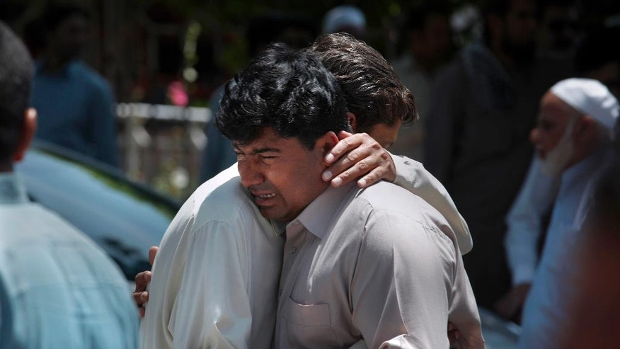 People comfort each other after funeral prayers of a victim of Friday's suicide attack in southwest Baluchistan province, in Islamabad, Pakistan, Saturday, May 13, 2017. The Islamic State group said it carried out the brazen suicide attack on a Pakistani lawmaker that killed 25 people despite a protracted crackdown on the assortment of militant groups operating in Pakistan. (AP Photo/Anjum Naveed)