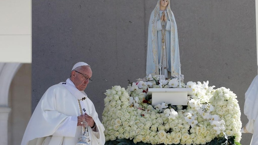 Pope Francis walks past a statue of the Virgin Mary prior to the start of a mass at the Sanctuary of Our Lady of Fatima Saturday, May 13, 2017, in Fatima, Portugal. The pontiff will canonize on Saturday two poor, illiterate shepherd children whose visions of the Virgin Mary 100 years ago marked one of the most important events of the 20th-century Catholic Church. (AP Photo/Alessandra Tarantino)