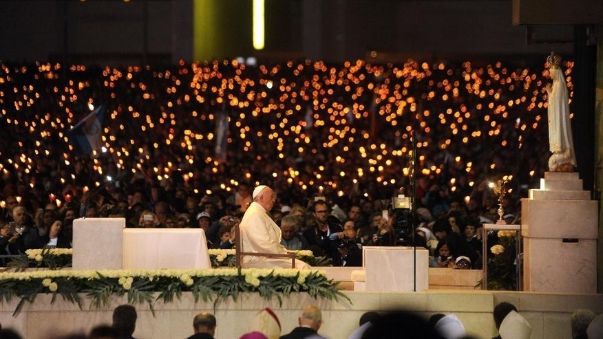 Pope Francis leads a candle light vigil prayer at the Sanctuary of Our Lady of Fatima Friday, May 12 2017, in Fatima, Portugal. Pope Francis will canonize on Saturday two poor, illiterate shepherd children whose visions of the Virgin Mary 100 years ago marked one of the most important events of the 20th-century Catholic Church. (AP Photo/Paulo Duarte)