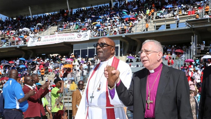 Palestinian Bishop Dr. Munib A. Younan, right, joins newly elected president Nigerian archbishop Musa Panti Filibus, centre as they attend a service, held in Windhoek, Namibia, Sunday, May 14, 2017. Thousands of members of the Lutheran church have gathered at a stadium in Namibia to mark the 500th anniversary of the Reformation. (AP Photo/Dirk Heinrich)