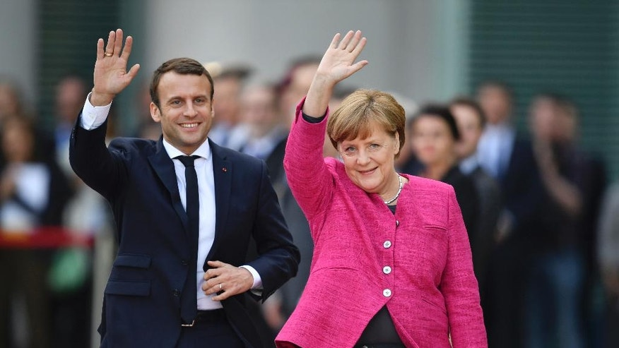New French President Emmanuel Macron, left, and  German Chancellor Angela Merkel wave to journalists at the chancellery  in Berlin Monday, May 15, 2017, during the first foreign trip of Macron after his inauguration the day before.  (Bernd von Jutrczenka/dpa via AP)