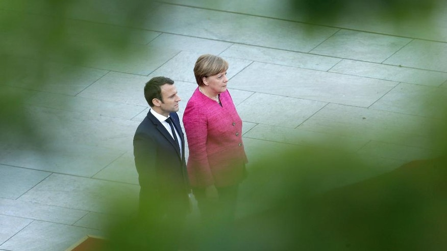 New French President Emmanuel Macron, left, and German Chancellor Angela Merkel listen to the national anthems during a military ceremony in Berlin Monday, May 15, 2017, during Macron's first foreign trip after his inauguration the day before. (AP Photo/Ferdinand Ostrop)