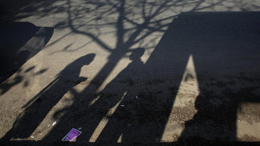 FILE - In this March 4, 2015 photo, the shadow of an Indian couple is cast on a road at the bus stop where the victim of a deadly gang rape had boarded the bus on Dec. 16, 2012, in New Delhi, India. (AP Photo/Altaf Qadri, File)