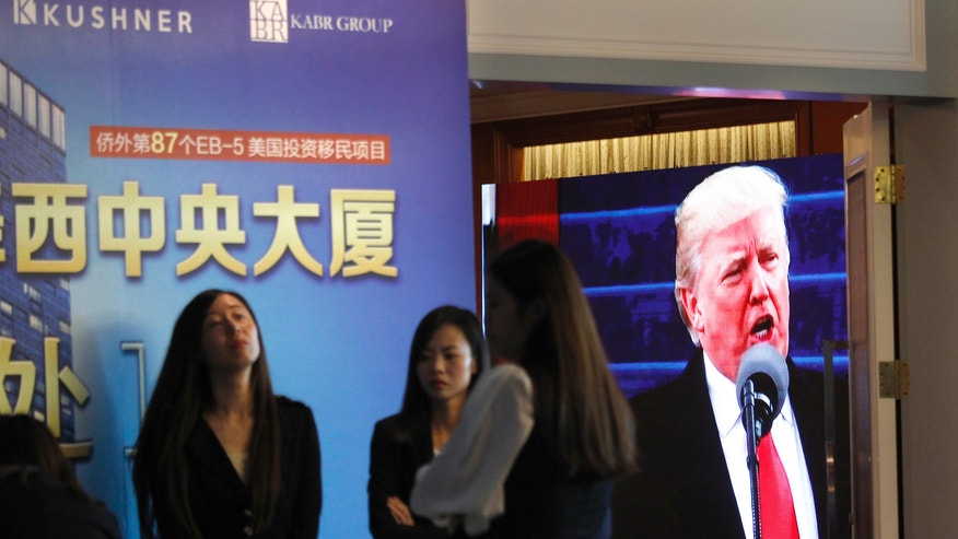 A projector screen shows a footage of U.S. President Donald Trump as workers wait for investors at a reception desk during an event promoting EB-5 investment in a Kushner Companies development, at a hotel in Shanghai, China, on Sunday, May 7, 2017. When the sister of Trump's son-in-law, Jared Kushner, promoted investment in her family's new skyscraper from a Beijing hotel ballroom stage earlier in the month, she was pitching a controversial American visa program that's proven irresistible to tens of thousands of Chinese. (AP Photo)