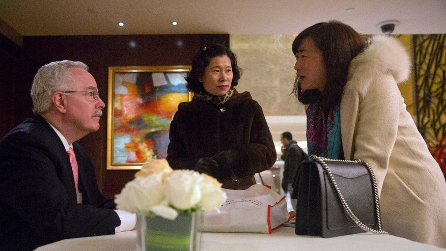 In this Sunday, Jan. 15, 2017 photo, Du Juan, right, talks to a consultant after a seminar by an investment group pitching ski resorts and other projects as a way of securing a EB-5 visa to immigrate to the U.S. in Beijing, China. She knows the potential danger of investing through the U.S. program, but she's willing to bear the risk as long as she can get her 10-year-old daughter enrolled soon in an American school. (AP Photo/Ng Han Guan)
