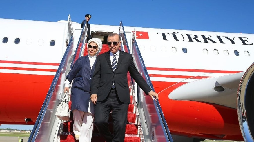 Turkey's President Recep Tayyip Erdogan and his wife Emine disembark from a plane after arriving in Washington, Monday, May 15, 2017. Erdogan is scheduled to meet U.S. President Donald Trump on Tuesday for talks expected to center on the friction between the two NATO allies over a U.S. decision to arm Syrian Kurdish fighters considered as terrorists by Turkey.  (Presidency Press Service/Pool photo via AP)