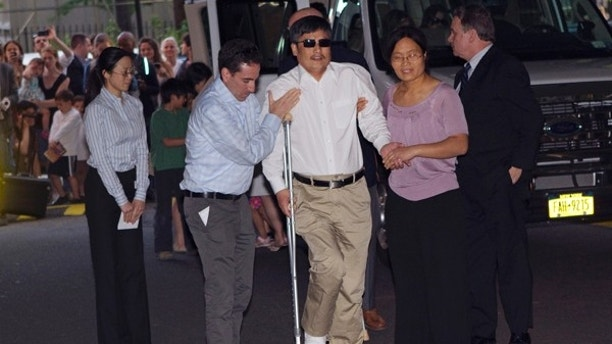 Blind Chinese dissident Chen Guangcheng (C) is helped by his wife Yuan Weijing (R) after arriving in New York May 19, 2012. Chen arrived in the United States on Saturday after China allowed him to leave a hospital in Beijing in a move that could signal the end of a diplomatic rift between the two countries. REUTERS/Keith Bedford (UNITED STATES - Tags: POLITICS) - RTR32BXI