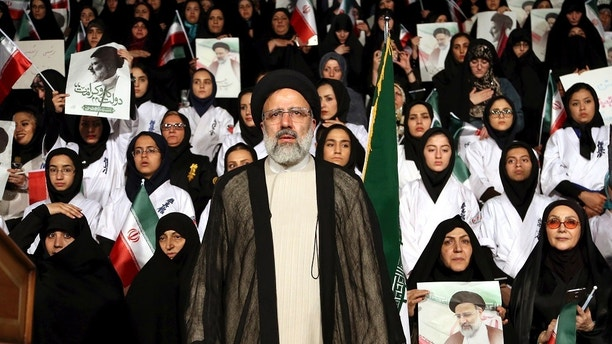 FILE -- In this April 29, 2017 file photo, Iranian cleric and presidential candidate Ebrahim Raisi, center, stands among his supporters, during a campaign rally in Tehran, Iran. From a former president disobeying the supreme leader to open discussion of a 1980s mass execution, Iran's presidential election is pushing the boundaries of what can be discussed and done there, a small but noticeable shift in the country's clerically overseen polls. (AP Photo/Ebrahim Noroozi, File)
