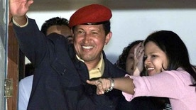 Venezuelan President Hugo Chavez (L) and his daughter Maria Gabriela wave to supporters from the balcony of the presidential palace while celebrating the first official results that showed Chavez with a clear victory over rival Francisco Arias in general elections held July 30, 2000. Chavez was reelected to a fresh six-year mandate in the this country of 24 million people.