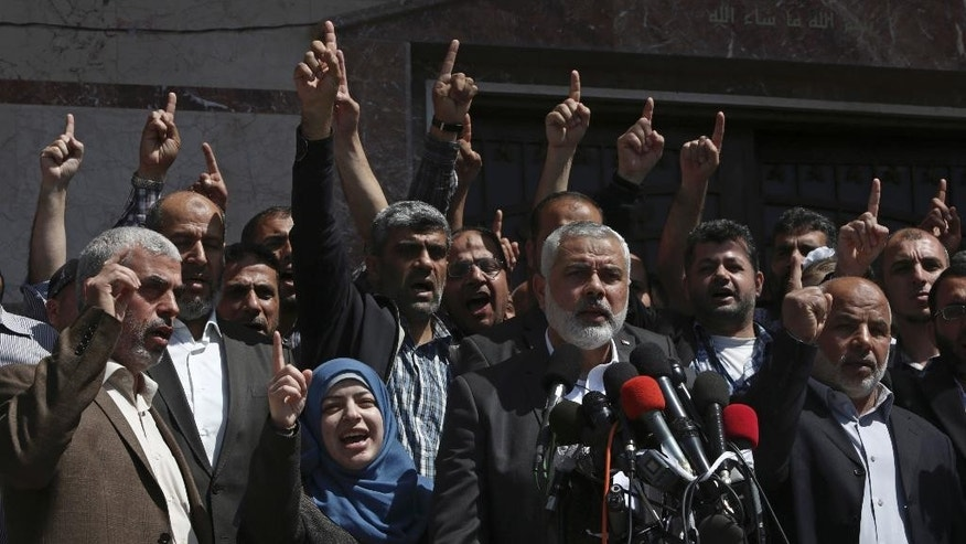 Supporters chant Islamic slogans as Hamas Supreme Leader Ismail Haniyeh, center, announces the arrest of a suspect in the March shooting death of Mazen Faqha, a top Hamas militant commander, in a hastily arranged news conference attended by Faqha's widow Nahed Asida, in front of Fagha's home, in Gaza City, Thursday, May 11, 2017. Haniyeh refused to identify the suspect, but said that Hamas had determined the gunman, apparently a local Palestinian, had acted on the orders of Israel and he expected the suspect would face execution. (AP Photo/Adel Hana)
