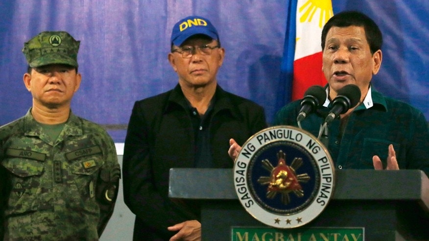 Philippine President Rodrigo Duterte, right, addresses troops during his visit to the 2nd Mechanized Brigade Friday, May 26, 2017 on the outskirts of Iligan city in southern Philippines. Duterte told the troops fighting Muslim militants for the control of southern Marawi city to use martial law powers to defeat the Islamic State group-linked extremists. At left is Armed Forces chief and martial law administrator Gen. Eduardo Ano and at center is Defense Chief Delfin Lorenzana. (AP Photo/Bullit Marquez)