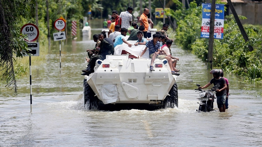 People are transported on top of an armoured personnel carrier on a flooded road as a man pushes his bike thorugh the water, in Bulathsinhala village, in Kalutara, Sri Lanka.