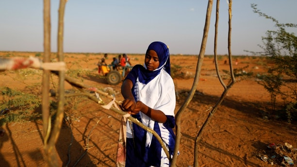 "Zeinab, 14, helps her mother and sister build a new shelter at a camp for internally displaced people from drought hit areas in Dollow, Somalia April 2, 2017.  REUTERS/Zohra Bensemra    SEARCH ""ZEINAB DOLLOW"" FOR THIS STORY. SEARCH ""WIDER IMAGE"" FOR ALL STORIES. - RTX34W3F"