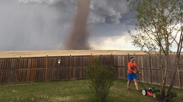 In this Friday, June 2, 2017, photo provided by Cecilia Wessels via The Canadian Press, Theunis Wessels mows his lawn at his home in Three Hills, Alberta, as a tornado swirls in the background. Cecilia Wessels, who took the image of her husband to show the tornado to her parents in South Africa, said that the twister wasn't as close it appears. (Cecilia Wessels/The Canadian Press via AP)