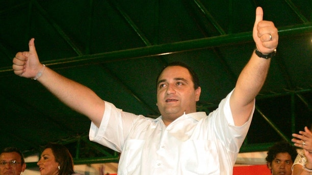 FILE - In this July 4, 2010 file photo, Roberto Borge, then candidate of the Institutional Revolutionary Party, PRI, for governor of the state of Quintana Roo, celebrates after preliminary results showed he held a lead in the state elections in Chetumal, Mexico.  Borge, a fugitive ex-governor wanted for alleged corruption in connection with the sale of state properties worth hundreds of millions of dollars was arrested in Panama, Mexican authorities said early Monday, June 5, 2017. A statement from the federal Attorney General's Office said Borge, who was governor of Quintana Roo from 2011 to 2016, was detained at the Panama City airport just as he was to board a flight to Paris. (AP Photo/Israel Leal, File)