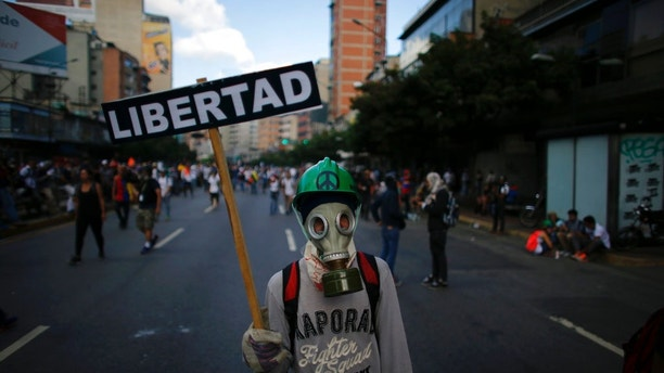 "A masked protester holds a placard that reads in Spanish: ""Liberty"" during clashes with government security forces in Caracas, Venezuela, Saturday, May 20, 2017. Tens of thousands took to the streets again in what has been two months of near-daily street protests. Demonstrators are demanding new elections and blaming President Nicolas Maduro for the nation's triple-digit inflation, rising crimes and vast food shortages. (AP Photo/Ariana Cubillos)"
