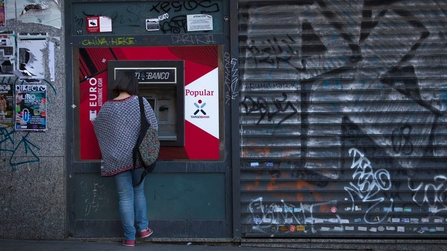 A woman uses a Banco Popular's ATM in Madrid, Wednesday, June 7, 2017. Spain's Banco Santander has acquired Banco Popular, the troubled lender that lost more than half of its shares value over the past week. (AP Photo/Francisco Seco)