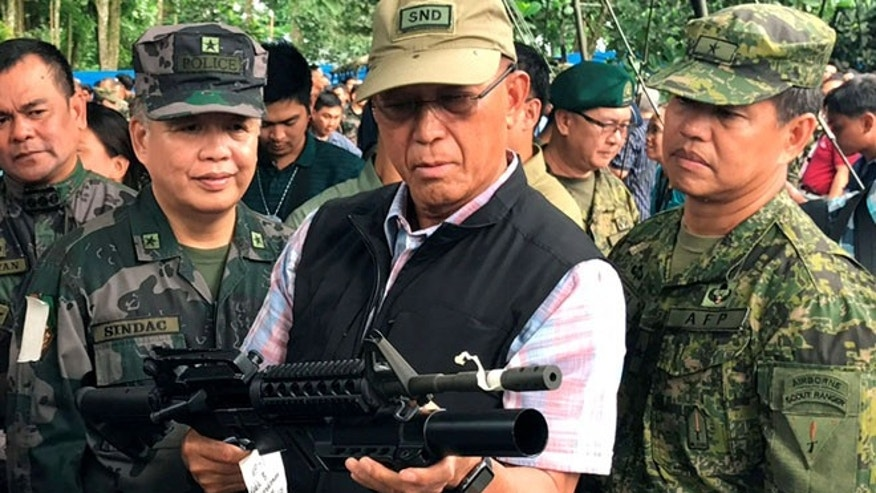 June 8: Philippines Defense Secretary Delfin Lorenzana (C) inspects a high-powered firearm seized from various hideouts of Islamist militants during their visit at a military camp in Marawi city